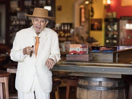 avo uvezian standing at bar table cigar boxes